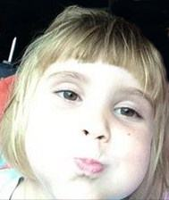 Photo of Olivia Cart, a little girl with blonde hair in bangs, very pale skin and brown eyes. She is pursing her lips and puffing her cheeks. The photo is taken from very close in, and is overexposed.