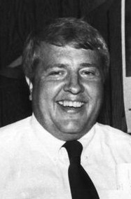 Black and white photo of Ed Dossett, a middle-aged, heavyset white man wearing a shirt and tie. He is smiling.
