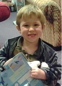 Photo of Dominic Elkins. He is a small boy with fair skin and blond hair. He is holding a toy in a plastic package.