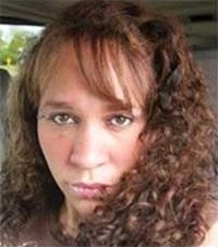 Photo of Barbara Getman, a Caucasian woman with curly brown hair and straight bangs that fall across her face.