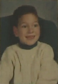Photo of Grant Heckman, a boy wearing a white sweater and smiling at the camera. He has fair skin and brown eyes and hair.