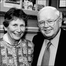 Black and white photo of Frank and Elizabeth Lackey. They have fair skin. She has dark hair and is wearing a sweater; he has light hair and is wearing a suit and glasses.