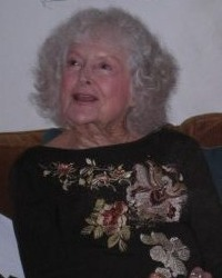 Photo of Irene McLean, an elderly woman with curly white hair and fair skin, wearing an embroidered sweater.