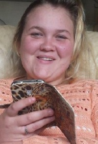 Photo of Jody Meyers. She has fair skin and blond hair with darker roots. She is holding a cell phone in a leopard-print cover, and wearing a silver ring and a peach sweater.