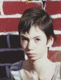 Photo of Sabrina Ray. She is a thin girl with pale skin and dark brown hair in a boy cut. Her expression is solemn.
