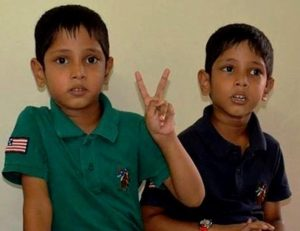 "Photo of Sarthak and Varad, twin boys. They have black hair and light-brown skin, and are wearing collared shirts, one green and one blue. The boy in the green shirt is holding up two fingers in a ""V"" sign."