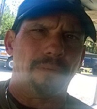 Photo of Charles Singer, a middle-aged man. He has a short brown mustache and beard and is wearing a blue baseball cap..
