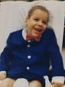 Photo of Trevor Horn, a little boy with olive skin and short curly brown hair. He is smiling. He is wearing a blue suit with a red bow tie that is a bit too big for him.