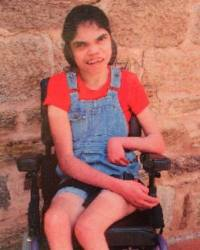 Photo of Kate Bugmy. She is a young woman sitting in a wheelchair, with her dark hair tied back. She is wearing overalls and an orange T-shirt. Her limbs are very thin.