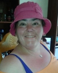 Photo of Carolyn Hyatt. She is a middle-aged woman with dark hair and fair skin, wearing a pink hat and blue-and-yellow tank top.