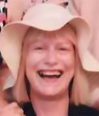 Photo of Julie Collier, a woman with straight blond hair, wearing a floppy hat. She is smiling.