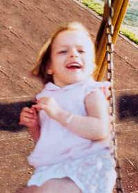 Photo of Andrea Lago, a blonde toddler sitting on a swing.