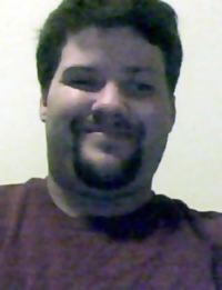 Photo of James Hill, an adult man with black hair and light skin. He is smiling. He has a short goatee and mustache.