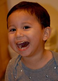 Photo of Pepe Castillo-Cisneros. He is a toddler boy with tan skin and dark brown hair, and is smiling widely with his mouth open.