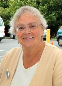 Photo of Dawn Green, an elderly white woman wearing glasses and a yellow shirt with a name tag pinned to it.
