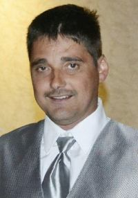 Photo of Martin Duram. He is a light-skinned man with dark hair and mustache, wearing a silver suit and tie.