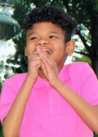 Photo of Ty Lee, a boy with light brown skin and dark brown hair, wearing a pink shirt. He has his hands raised to his mouth and is smiling widely.