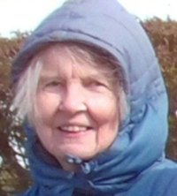 Photo of Meryl Parry. She is an elderly woman with fair skin and white hair. She is outdoors, wearing a blue coat with the hood up.