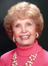 Photo of Nada Bodholdt. She is an elderly woman with strawberry blonde curly hair, cut short. She is wearing a pink turtleneck, earrings and a necklace.