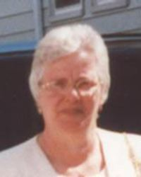 Photo of Maria Branco. She is an elderly woman with short white hair, and fair skin. She is wearing glasses and a white blouse, squinting slightly into the sun.