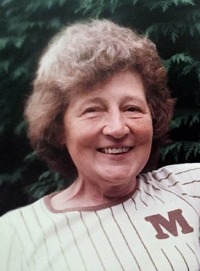 "Photo of Margaret Meyer, an elderly woman with curly gray hair and fair skin. She is wearing a sports jersey with the monograph ""M"" on it."