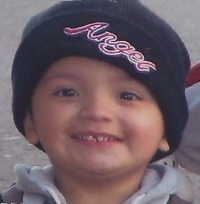 "Yonatan Aguilar, a boy of about four or five years old, has fair skin and is smiling at the camera. He is wearing a black knit cap embroidered with the word ""Angel""."