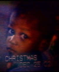 "Photo of Deetrick Brown. It is a photo of a TV screen, showing an African-American toddler with a solemn expression. Faint text along the bottom says, ""Christmas. December 25."" The rest of the text is indistinct."