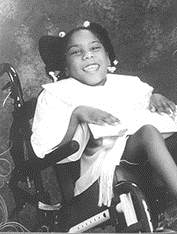 Black and white photo of Janelle Johnson. She is a young African-American girl in a white dress, sitting in a power wheelchair and smiling.