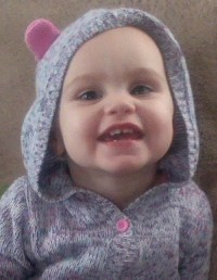 Photo of Maddox Lawrence, a baby with fair skin. She is wearing a gray knit jacket with a hood.