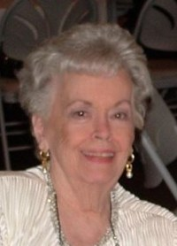 Photo of Shirley Neumann, an elderly woman with short gray hair. She is wearing a white blouse and earrings.