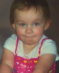 Photo of Tianna Kirchner. She is a baby girl with brown hair and fair skin, wearing a pink and white dress.