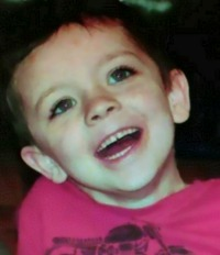 Photo of Tyler Caudill, a young boy with fair skin and brown hair. He has a wide smile. He is wearing a magenta T-shirt.