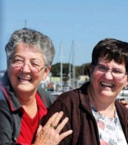 Photo of Janice and Robyn Frescura. Janice is an older woman with fair skin and gray hair; Robyn is a middle-aged woman with brown hair and fair skin. Both women are wearing glasses, shirts and jackets.