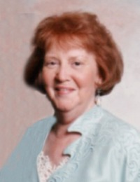 Portrait photo, slightly blurry, of a woman in late middle age. She has fair skin and red hair.