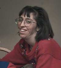 Photo of Cindy Enger. She is a woman with pale skin and brown hair, wearing large glasses and a red sweater.