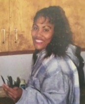 Photo of Sonia Riang, an African-American woman with medium-brown skin and curly black hair. She is wearing a flannel jacket and smiling.