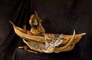 "Photo of ""Athabaskan Male Doll with Accessories"", artwork by Riba Dewilde. The doll is made of wood, bark, fur, and antler. It is dressed in traditional clothing, sitting in a canoe and holding a fishing spear."