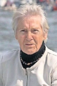 Photo of Rietje Willms, an elder woman. She has short white hair and fair skin, and is wearing a black turtleneck and white jacket. Her expression is solemn, and she is squinting slightly into the sun.
