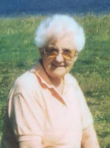 Photo of Addison Avis, an elder woman with short, curly white hair and fair skin. She is wearing a pale peach blouse and tinted glasses, and is smiling for the camera.