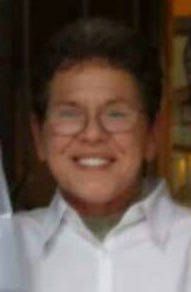Photo of Rebecca Benight. She is a middle-aged woman with short curly brown hair, fair skin, and brown-rimmed glasses. She is smiling at the camera.