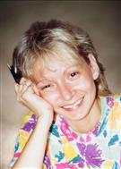 Photo of Jocelyne Lizotte, a middle-aged woman with graying light-brown hair cut to chin length. She is leaning her head against her hand, smiling, and wearing a flower-print shirt.