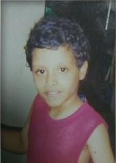 Photo of Matthew Tirado, a young boy with light-brown skin and curly black hair. He is wearing a red tank top.
