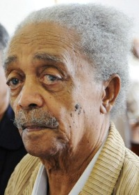 Photo of Peter Abrahams, an elderly African man with medium-brown skin and white hair and mustache.