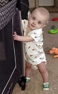 Photo of Aedyn Agminalis, a baby with fair skin and wispy blond hair. He is wearing a onesie and holding on to a piece of furniture to support him as he stands on wobbly legs.