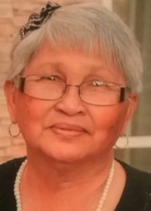 Photo of Gertrudes Hollis, an older woman with tan skin and short white hair, wearing glasses and a pearl necklace.