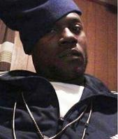 Photo of Troymaine Johnson, an African-American man wearing a navy windbreaker and blue knit cap.
