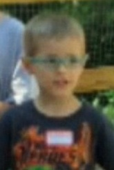 Photo of Daniel Schlemmer, a young boy wearing glasses and a navy T-shirt with a name tag on it. He has short blond hair and fair skin.