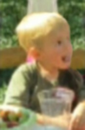 Photo of Luke Schlemmer, a toddler boy with fair skin and blond hair. He is sticking his tongue out and smiling.