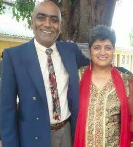 Photo of Prakash and Shoba Singh. He is a middle-aged man wearing a suit and tie; his skin is medium-brown and his head is shaved. She is wearing a dress with a red sash, has light-brown skin and curly short gray hair.