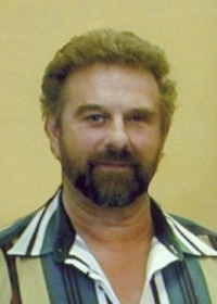 Portrait of David Leath. He is a middle-aged man with curly brown hair and beard and light skin; he is wearing a striped shirt.